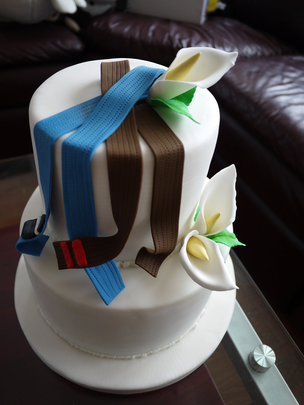 Jujitsu Belts - Diana and Ben asked us to create a groom's cake to go alongside the cake being provided by their wedding venue. At the time, Diana was a brown belt in jujitsu and Ben was a blue belt in Brazilian jujitsu. Made with sugar are the belts and calla lilies that top the two-tier cake.Delivered: July 7, 2012