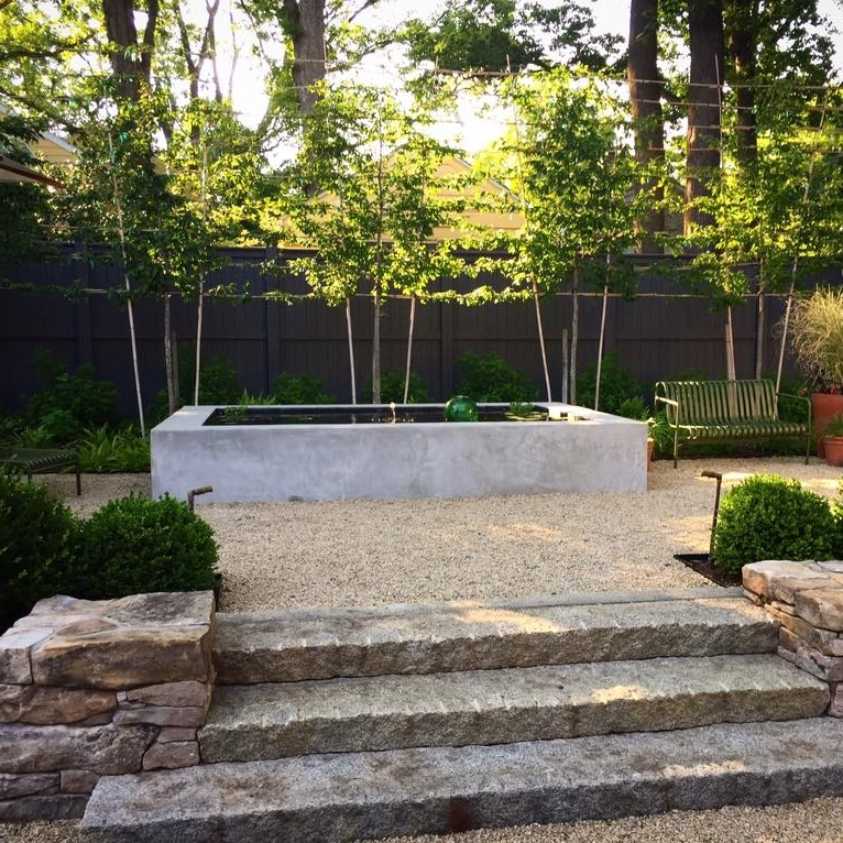 A crisp concrete water feature provides a modern counter to a traditional garden layout.