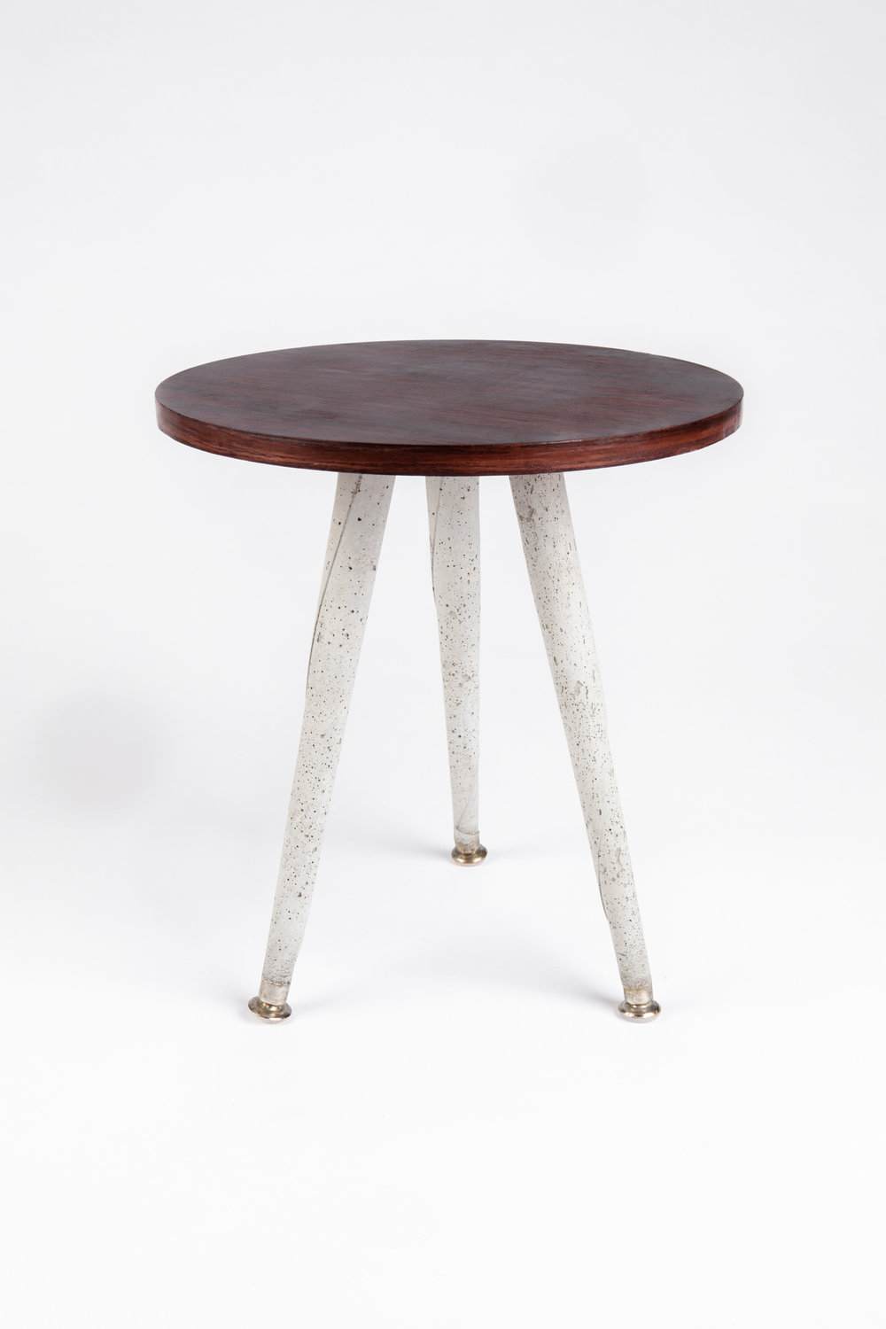 "TA KA TSI KA  rosewood table top, cement legs & steel leg mounts 15"" height x 15"" diameter  This side table is named Ta Ka Tsi Ka, mimicking the sound of Brazilian drums. It looks great on its own and is at its very best when paired with its mirror image (the Ka Tsi Ka Ta side table). The concrete legs of Ta Ka Tsi Ka are unexpected, while the smooth, soft texture of Ka Tsi Ka Ta's top clashes with its seemingly rough surface."