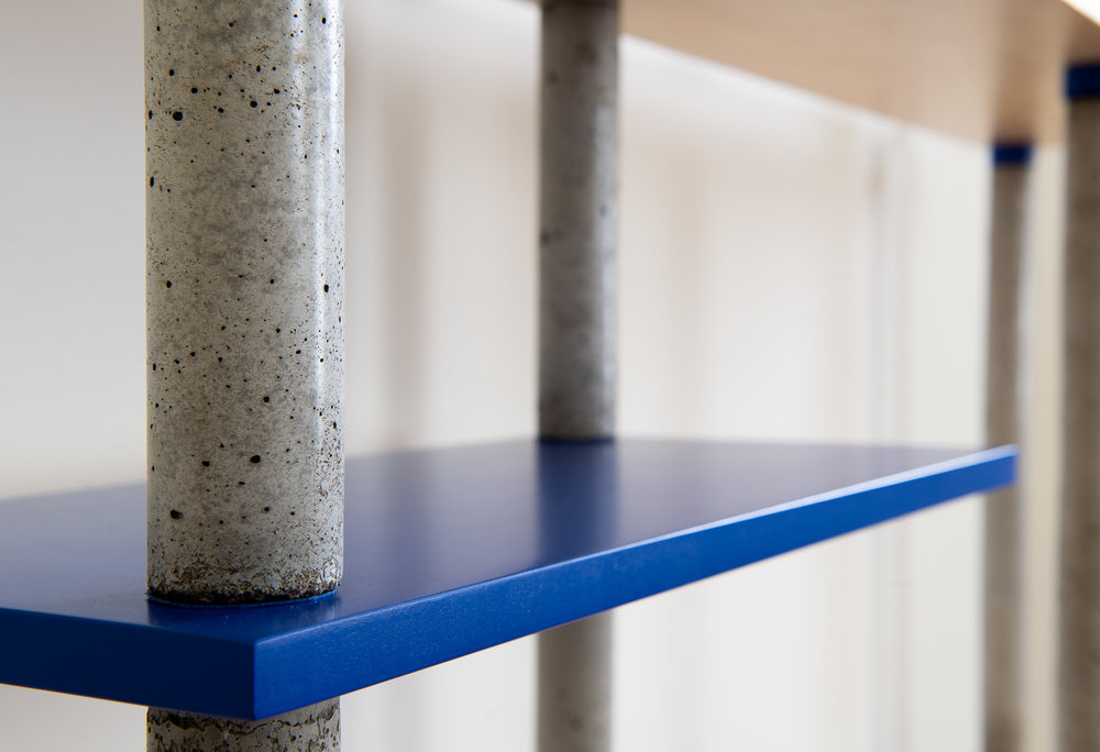Concrete bookcase pillars with cobalt blue shelf