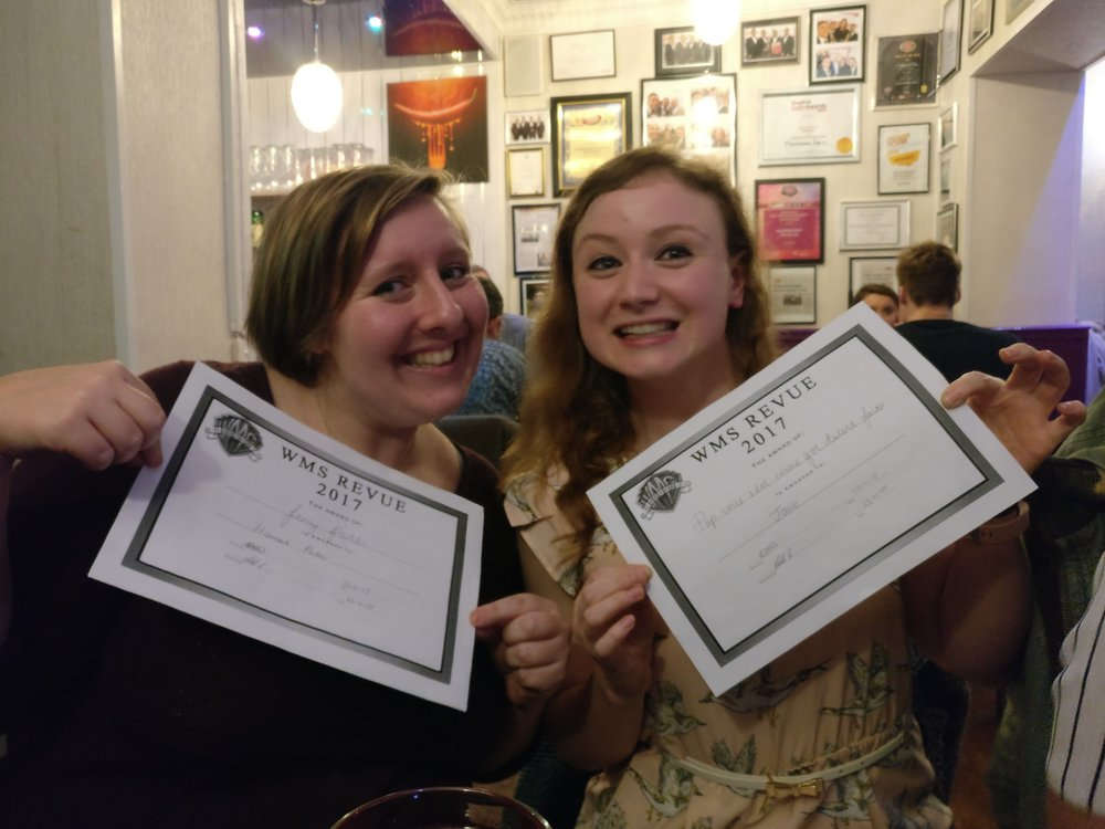 Two cast members with their peer-nominated awards ('Fancy Pants - Best Costume' and 'Best Vocals')