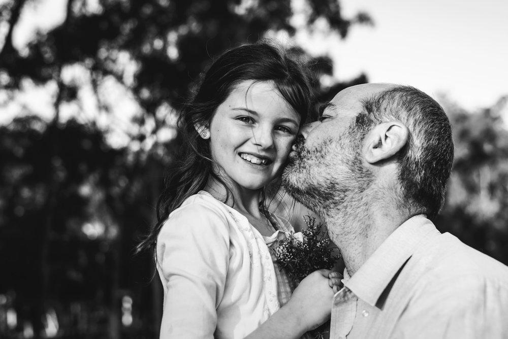 dad kissing daughter's cheek