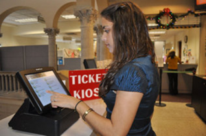 A customer tries Coral Gables' new automated customer management system in its Building and Zoning department. The kiosk system is designed to guide customers to the correct line so as to minimize wait times.