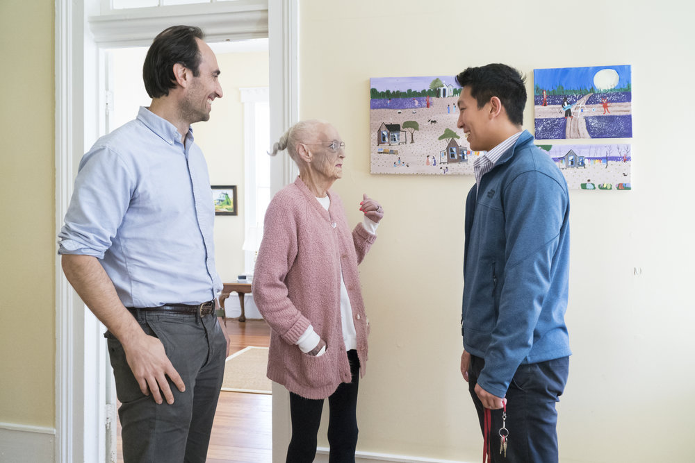 Dr. Dorsey and Kevin Wang, 2017-18 Fellow, speaking with one of the housing program residents.