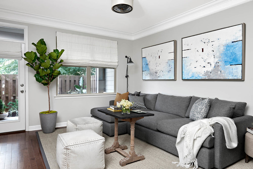 White And Gray Living Room Area With White Leather Cube Stools, Dark Wood  Floors