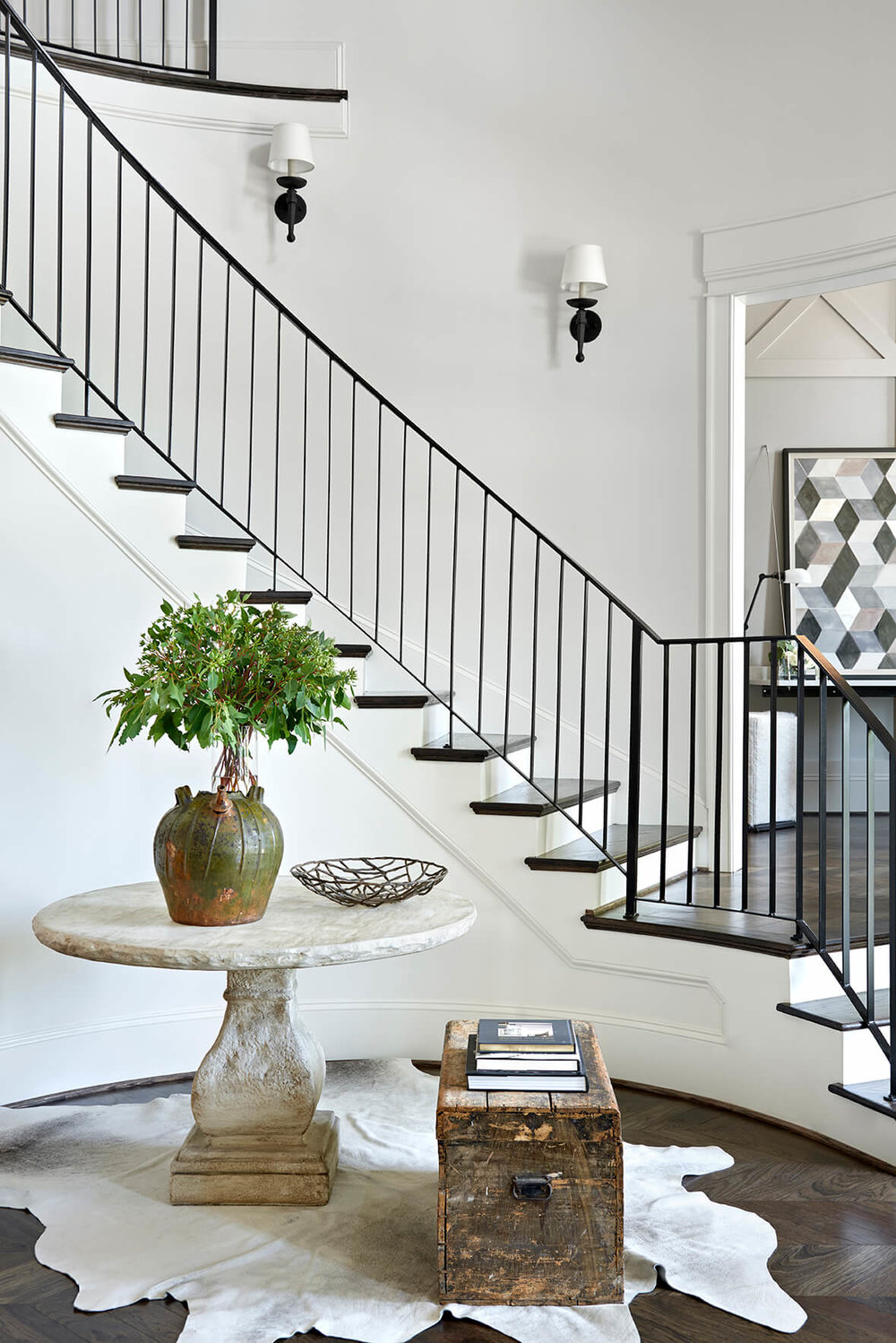 Staircase with dark stairs, side table on an animal skin rug - Rustic Contemporary Bureau Interior Design Nashville TN