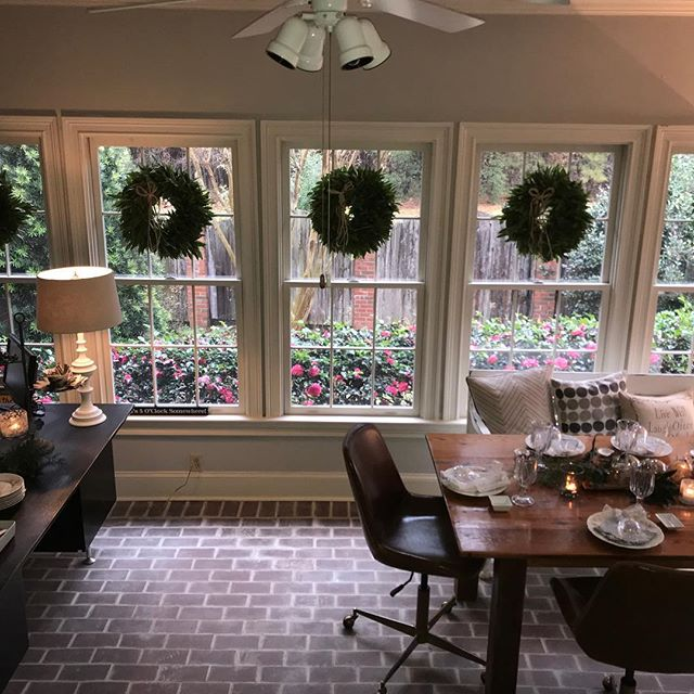 Purchased fresh bay leaf wreaths @mcfadden.farm for clients, family and friends and made the mistake of hanging them in my sunroom...Merry Christmas to me!  Definitely new tradition ❤️! Please swipe to see more pics.  #wreath #bayleaf #bayleafwreath #brick #brickfloor #holiday #holidaydecor #christmas #ornaments #christmasornaments #christmasdecorations #mirror #reclaimedwoodmirror #reclaimedwood #reclaimedwoodfurniture #farmtable #leather #leatherchair