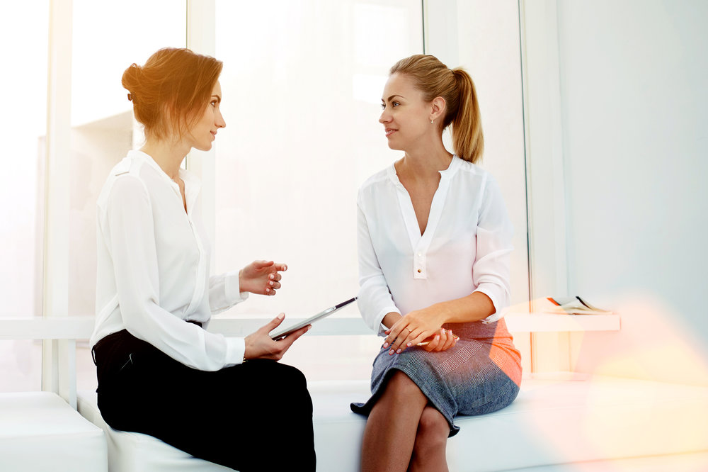 female-business-owners-discussing-work-at-desk.jpg