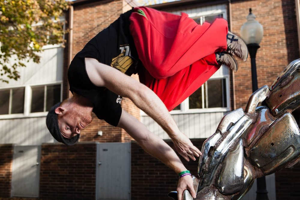 Kurt performing a palm spin on one of the metal horse sculptures at Sedgwick & Wisconsin. Photo by David Yip.