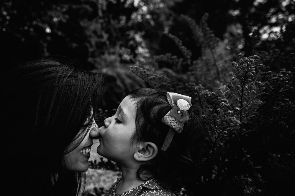 Mum and daughter tender kiss - documentary family photography Cambridge