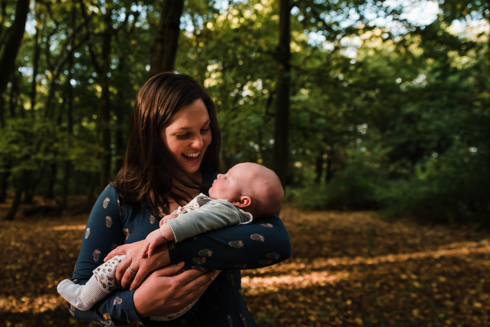 Mother cradles baby with joy in a park - baby documentary photographer