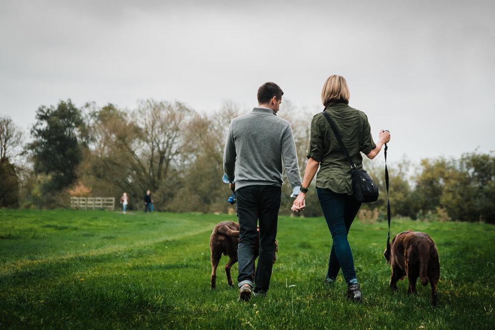 Couple holding hands on a walk in Grantchester Meadows