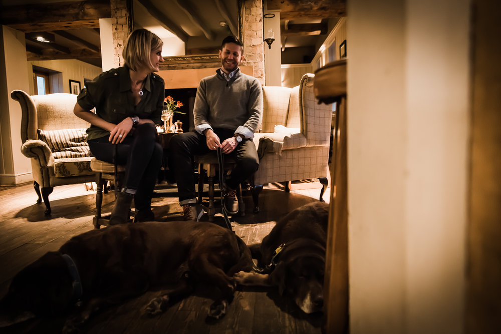 couple laughing together and dogs sleeping in the pub
