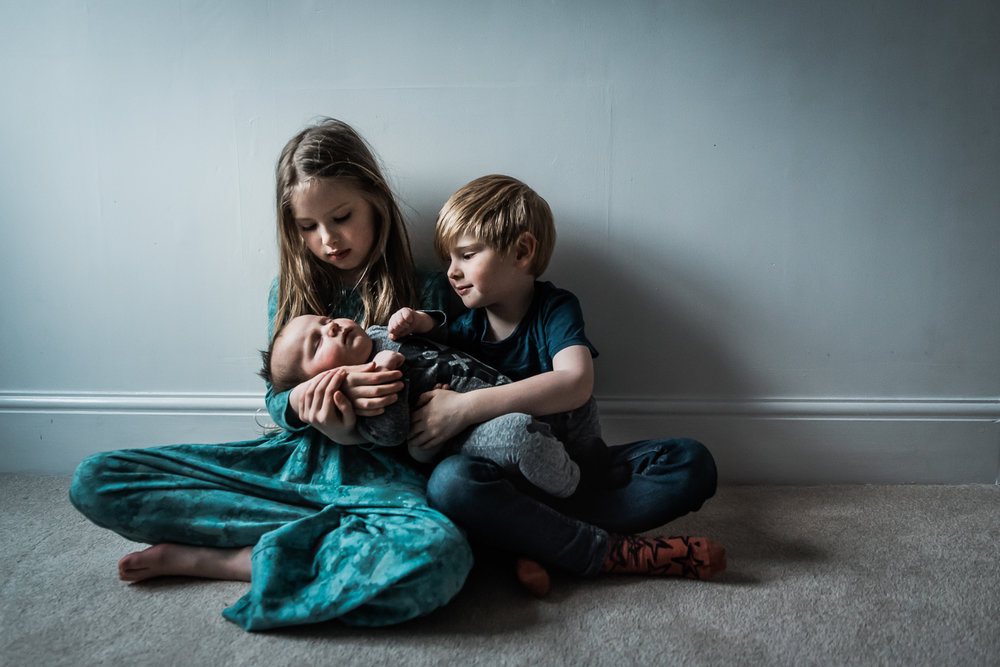siblings holding baby brother beautiful window light