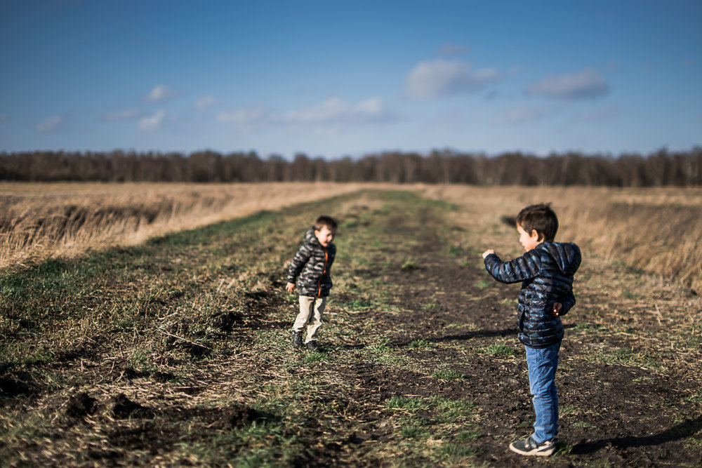 Two boys standing in open field looking towards Holme Fen