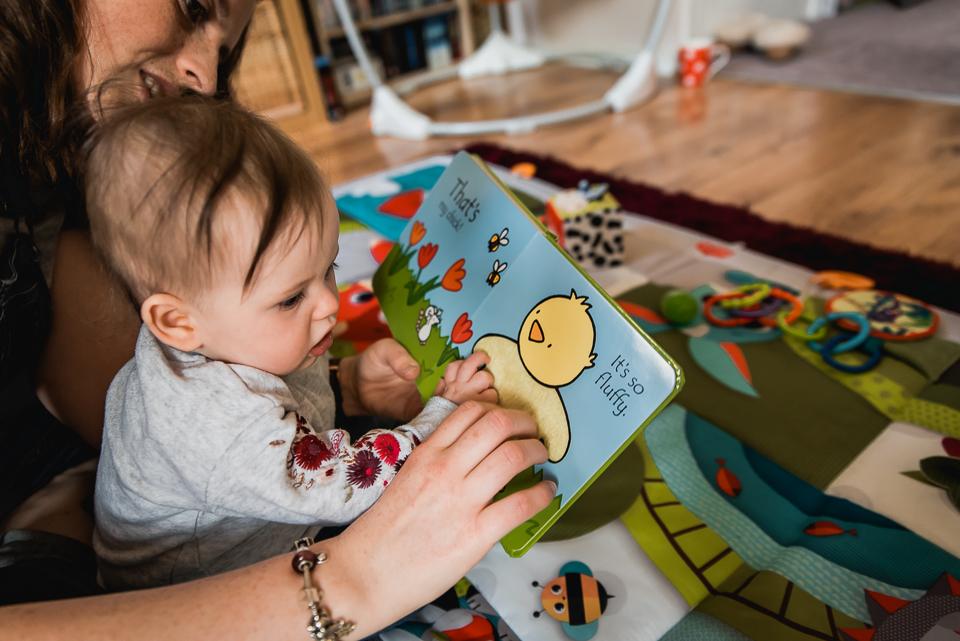 Mum reads books to her baby