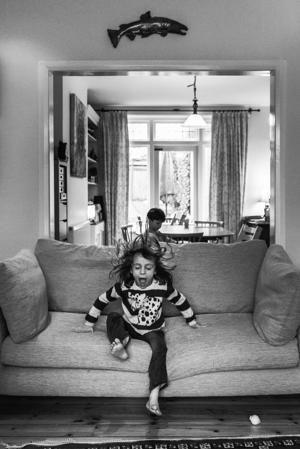 Copy of Black and white photograph of girl landing on the sofa