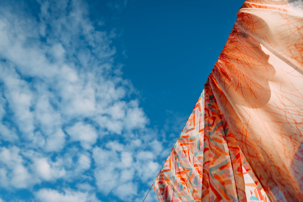 Scarves on the washing line flying high in the blue sky