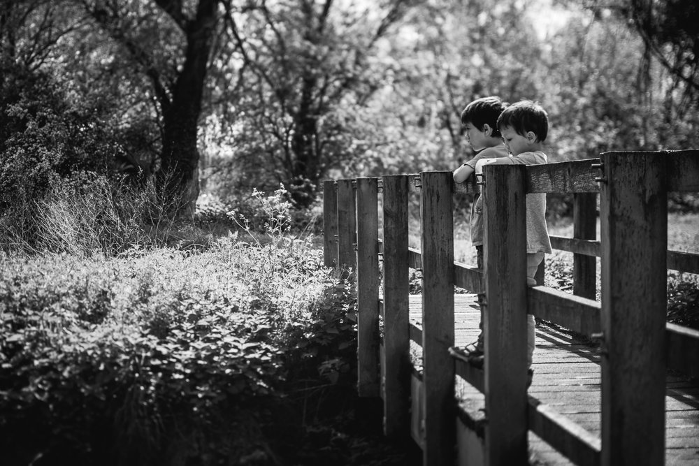 Two children standing on the bridge black and white photograph