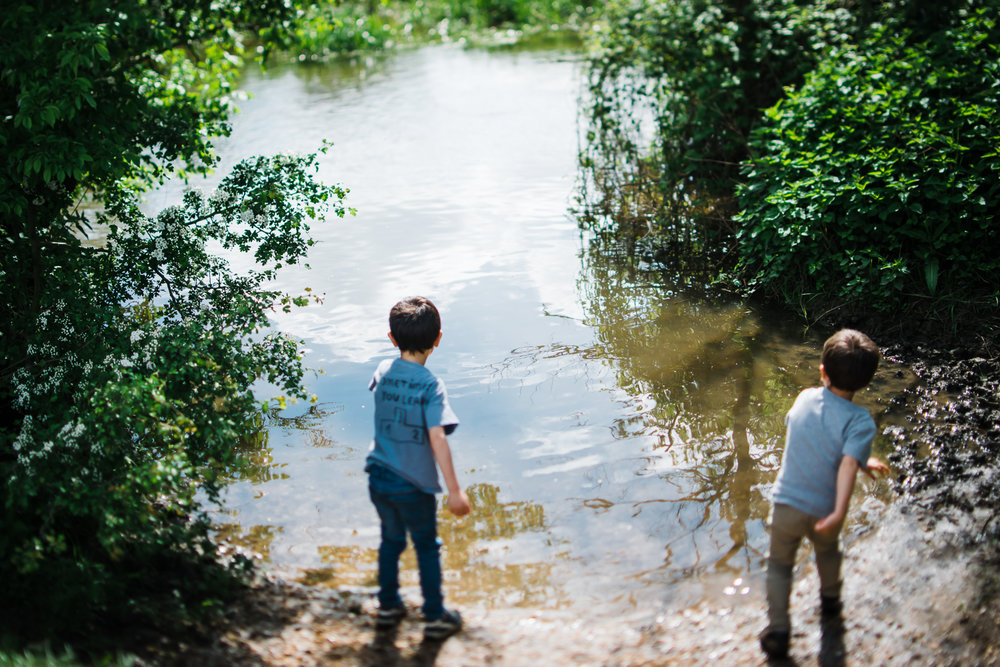 Two children throwing stones in a river.