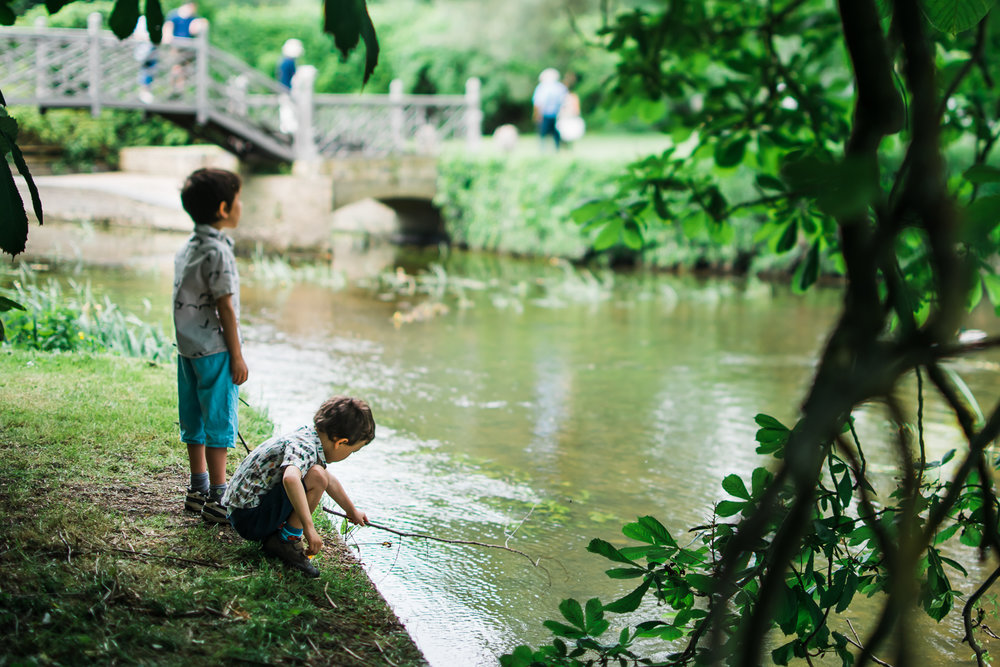 Boys playing by the river in the garden of Island Hall, Godmanch