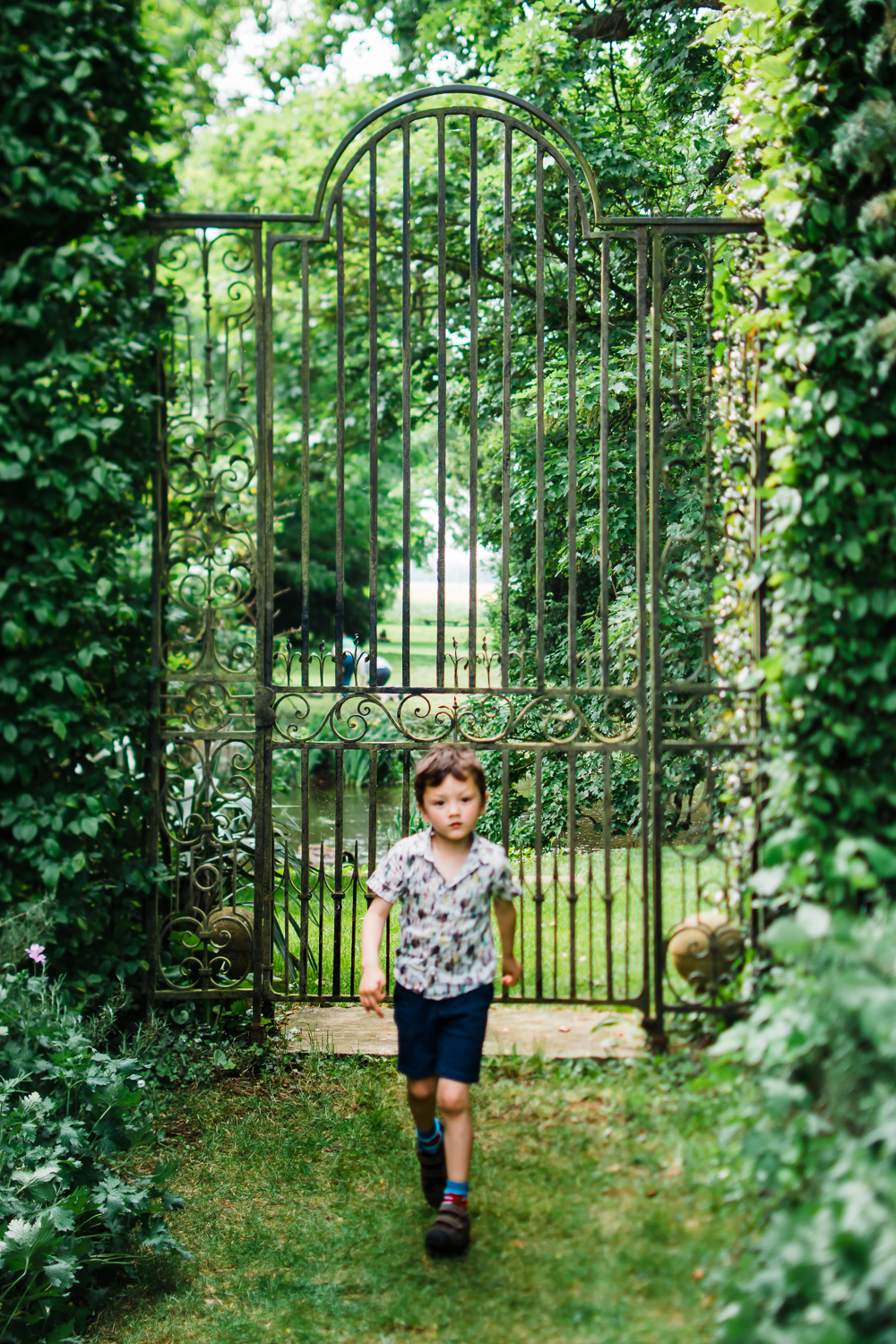 Boy walking in front of gate at Island Hall garden, Huntingdon