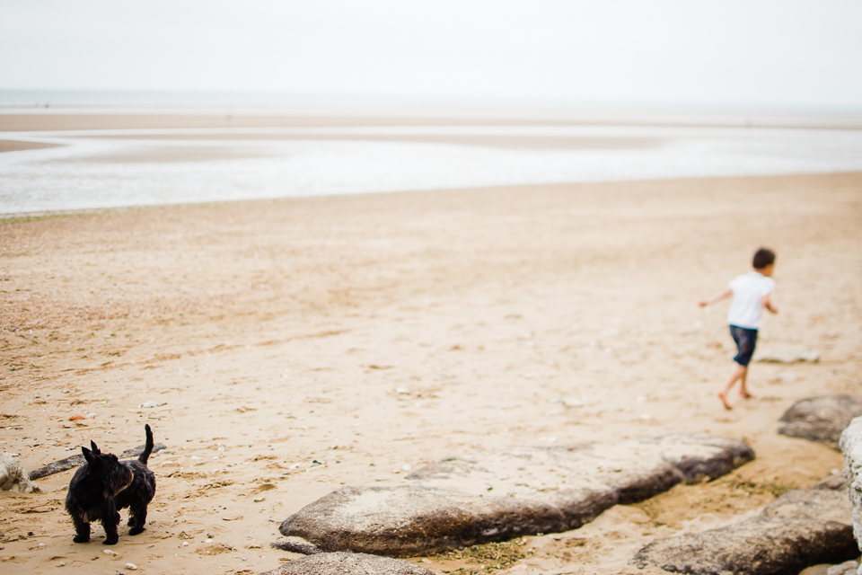 Freelensed photograph of young boy and his dog on the beach on t