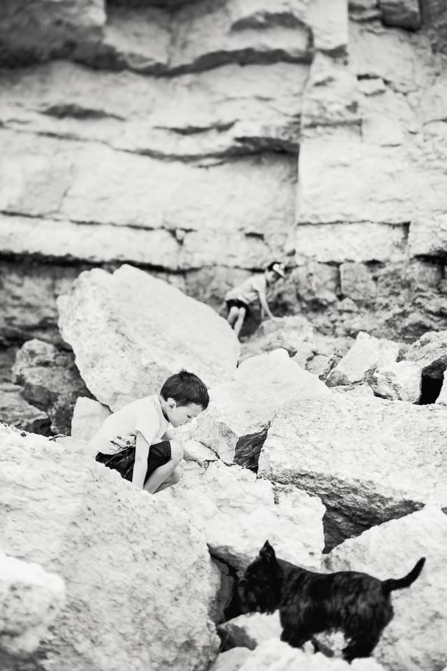 Children climbing rocks at Hunstanton cliffs in black and white