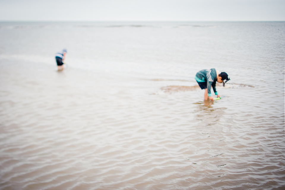Two children having a dip in the sea in North Norfolk