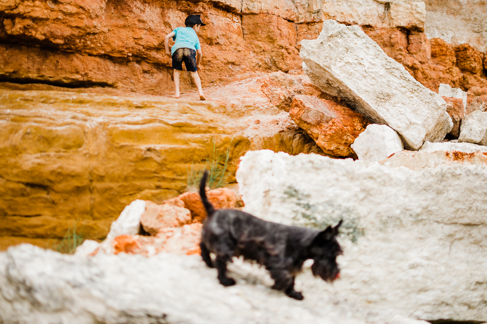 Boy and his dog climbing on the red and white sandstone rocks at