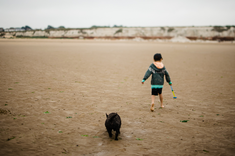 Boy and his dog walking on the beach at Hunstanton beach