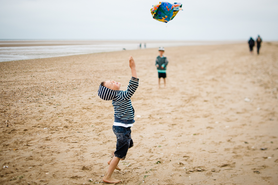 Young boy attempts to fly his kite at Hunstanton beach