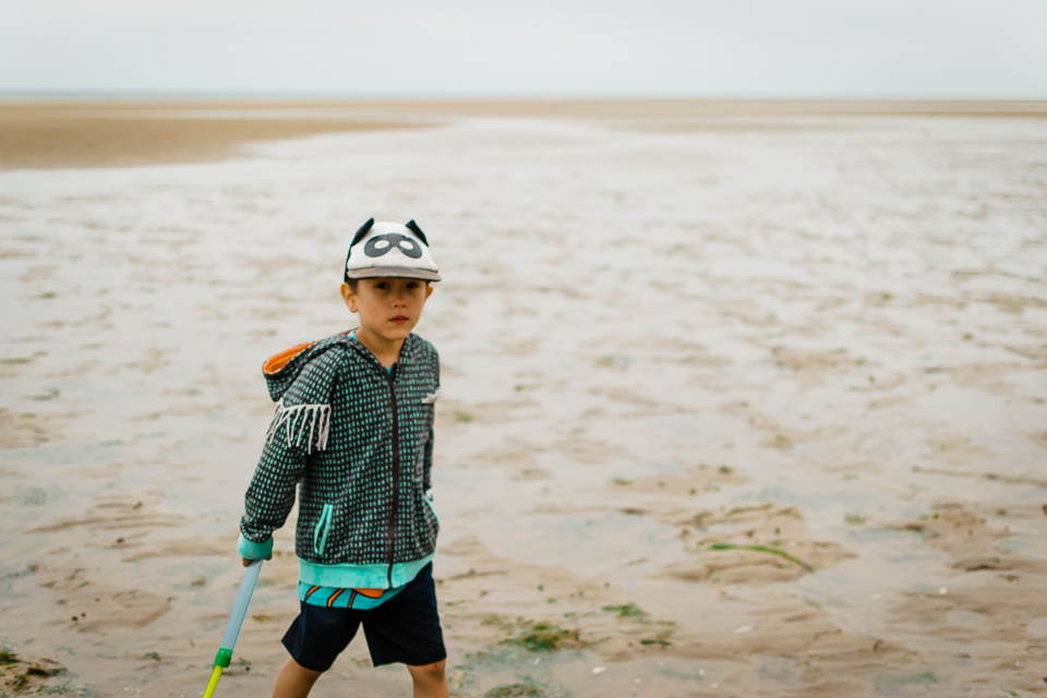 Boy with a bat mask cap on the beach in Hunstanton