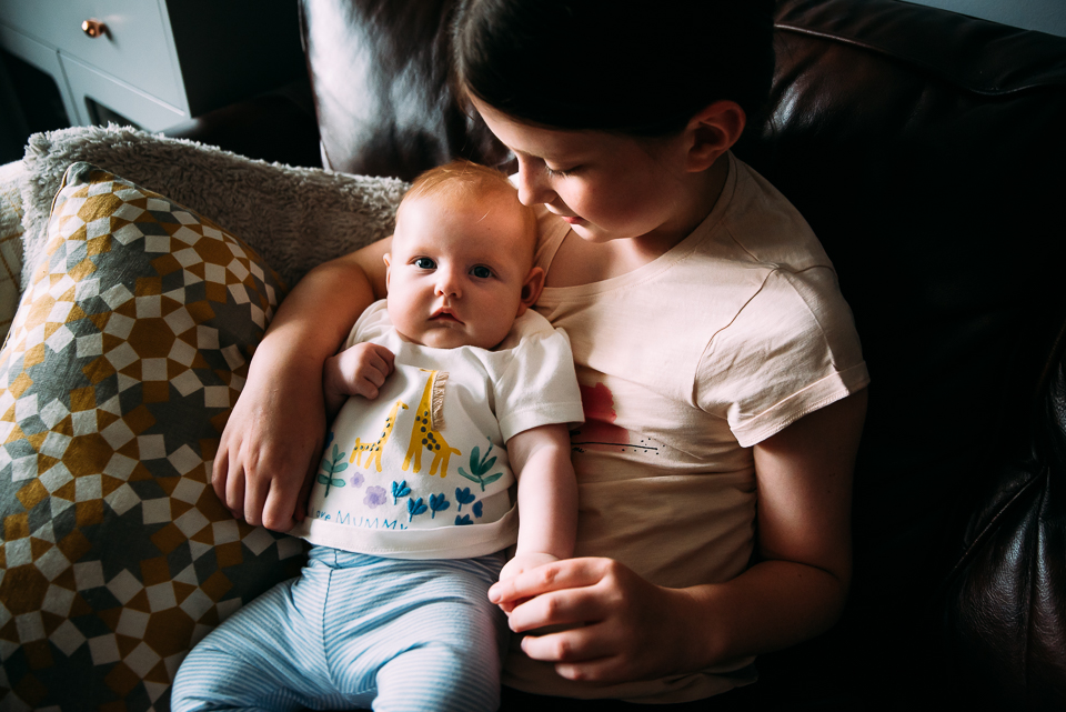 Girl holding her baby sister at home