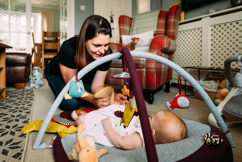 Mother plays with her baby on the playmat