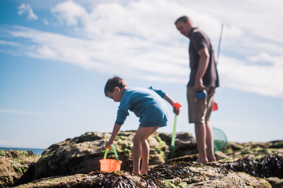 Father and son on the beach rocks with an orange bucket and wate