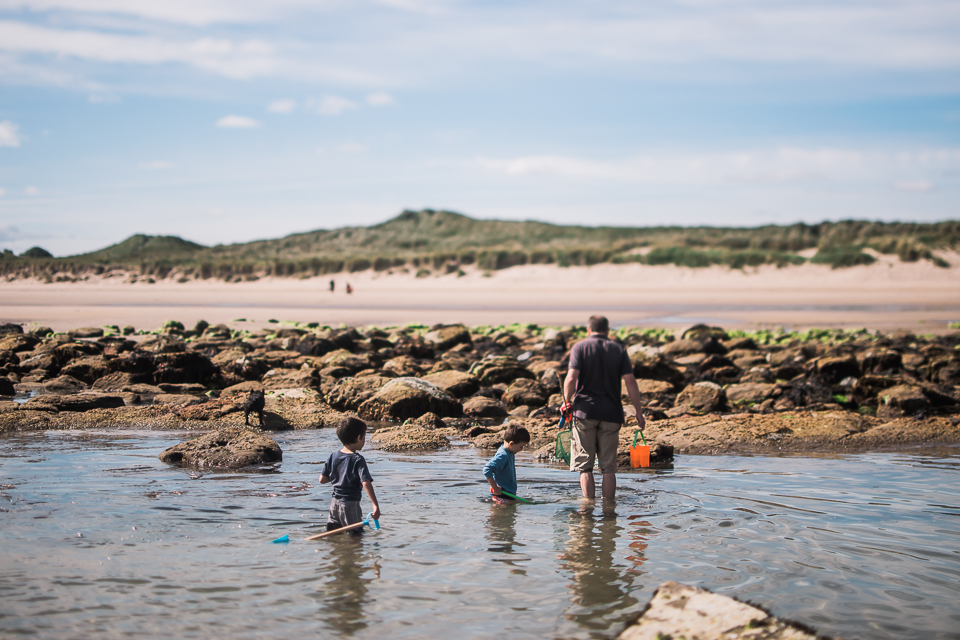 Wading through the waters in the rockpools at Bamburgh Beach