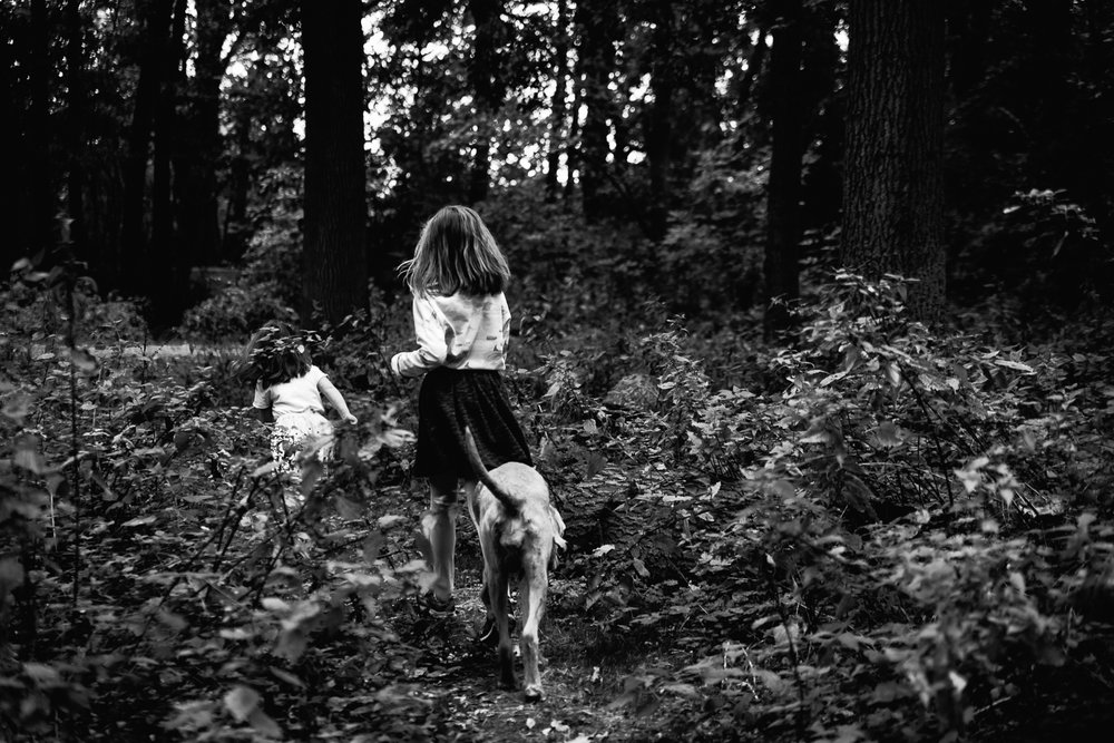 Children running  through the woods black and white photograph
