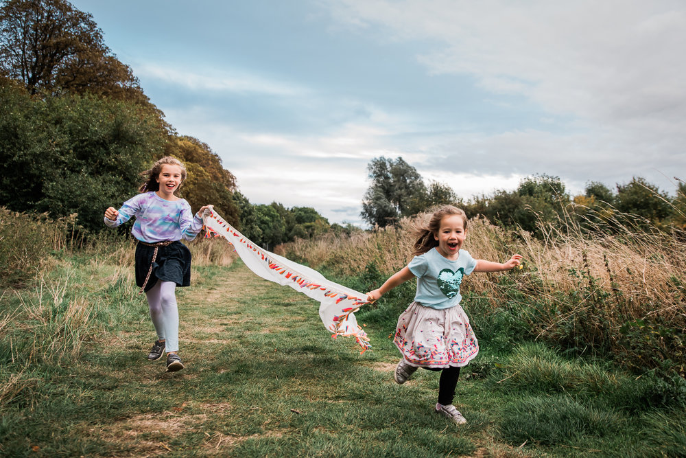 Children running with a colourful scarf down a grass path