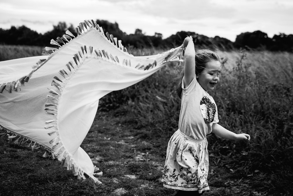 Black and white photograph of a girl running with a scarf in her