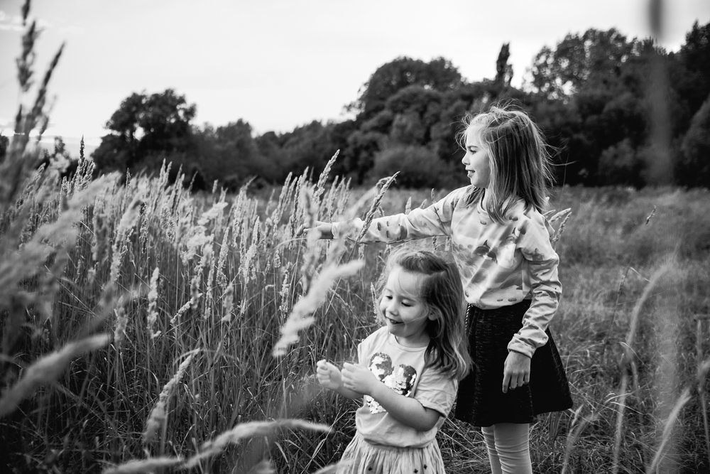 Two sisters playing amongst the grass
