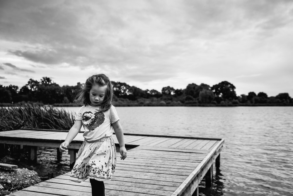 Black and white photograph of a girl by the lake