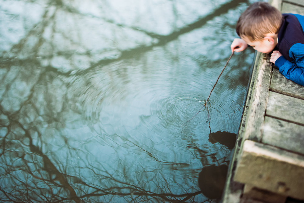 Boy dipping a stick into the water creating ripples