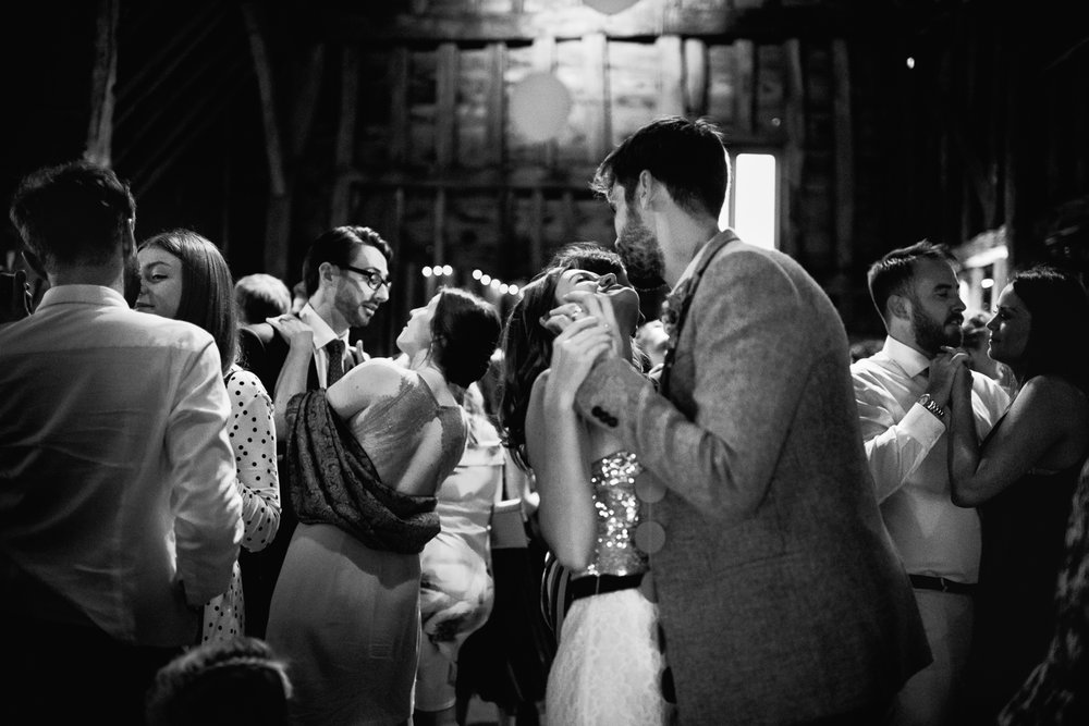 Black and white photograph of couples dancing together at a barn