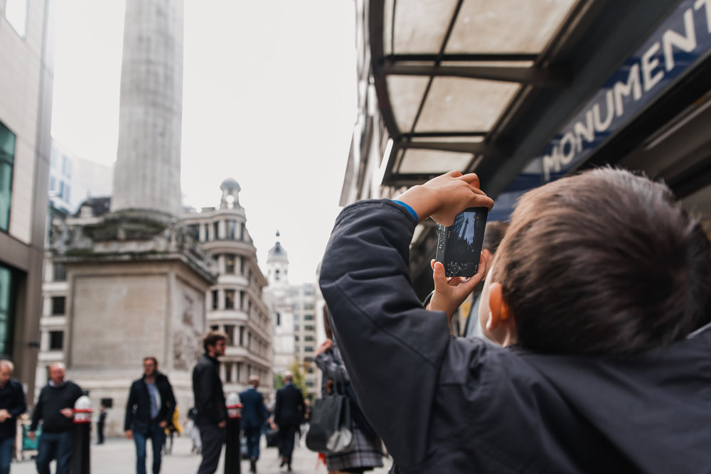 Boy taking a photo of The Monument outside Monument tube station