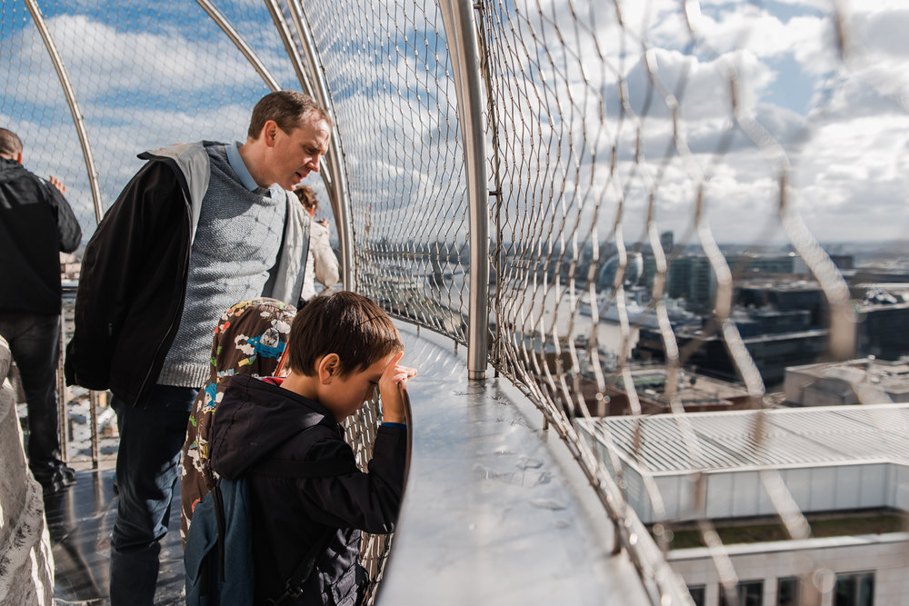 A father and son stands at the top of The Monument looking down