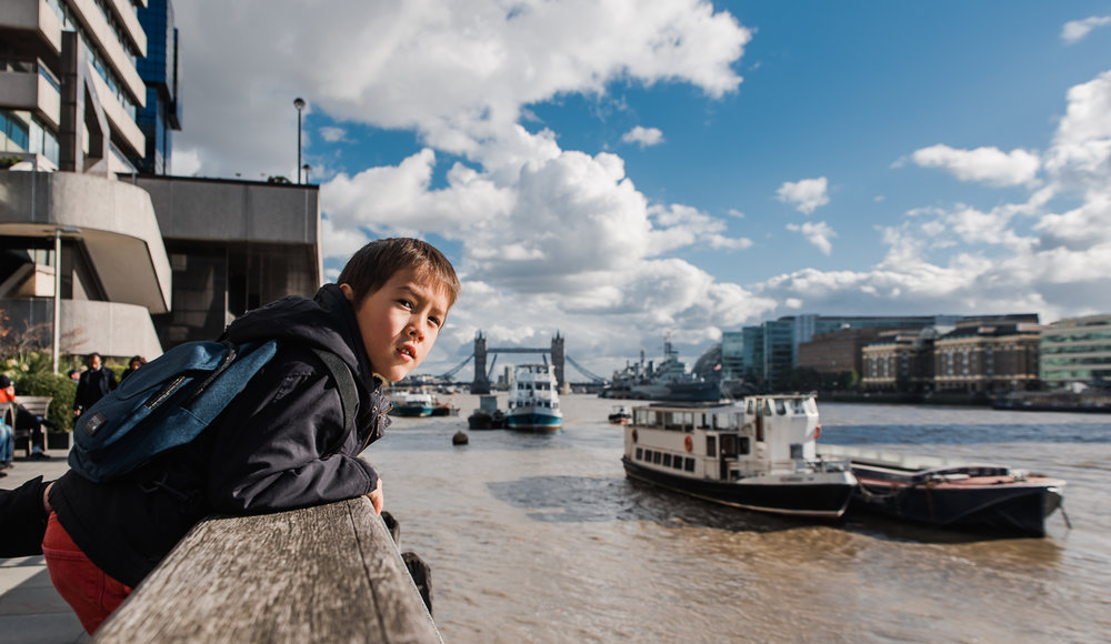 A photo of a boy leaning over the side by the river Thames with