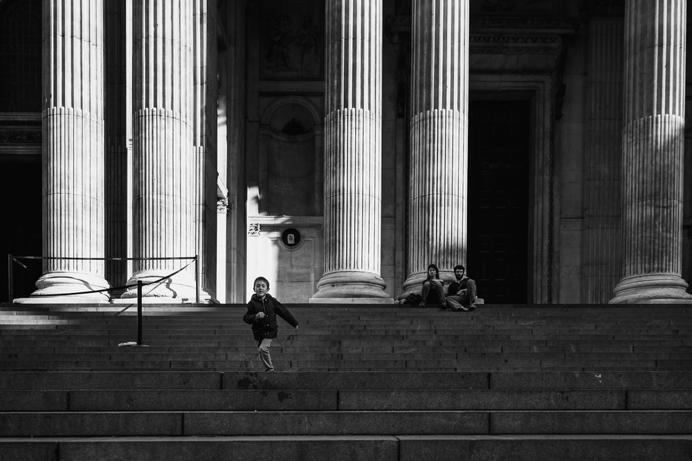 Boy running down the steps of St Paul's cathedral black and whit