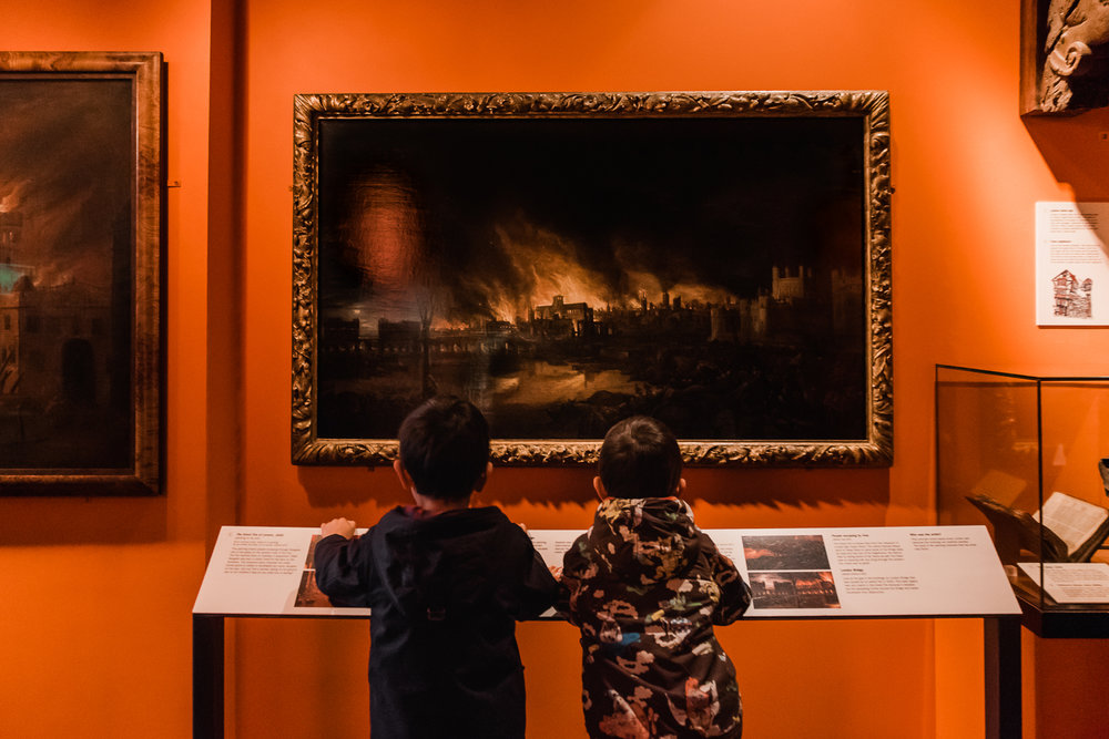 Two children looking at the painting of the Great Fire of London