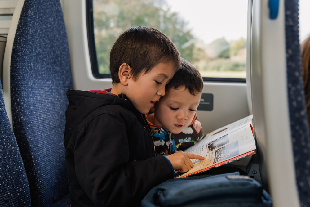 Two children reading a book on the train